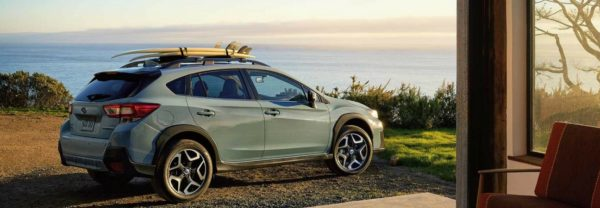 2018 Subaru Crosstrek parked outside a modern home facing an ocean