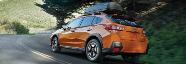 An orange 2018 Subaru Crosstrek driving up a mountainous road