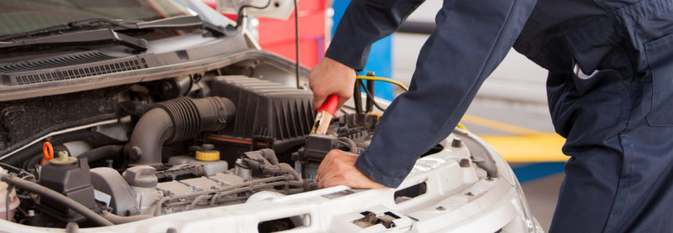 Auto mechanic hooking up a jumper cable to a car battery